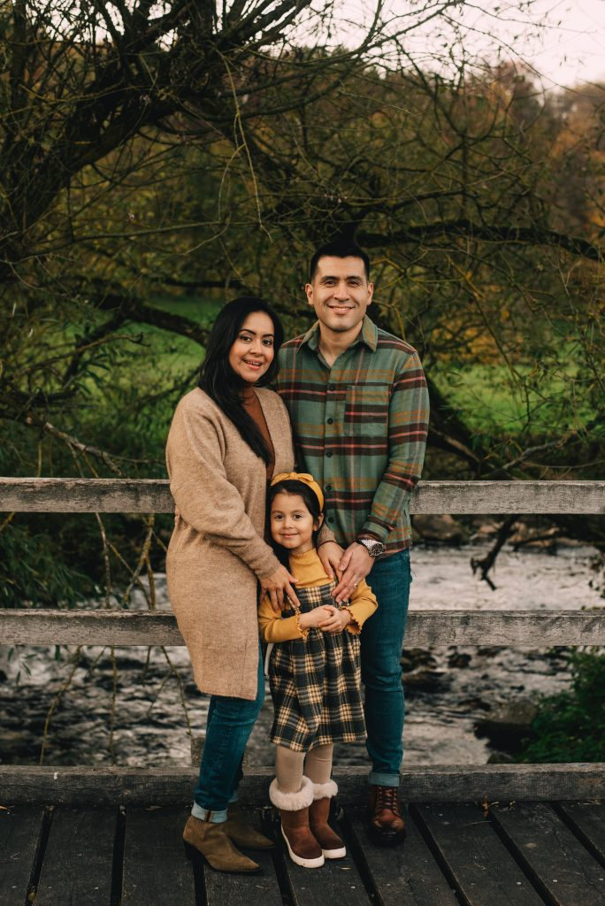 Family of 3 posing by the river