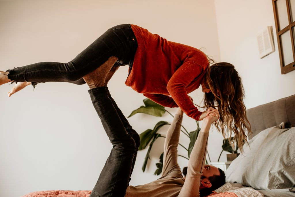 Man lifting up woman in bed with his legs